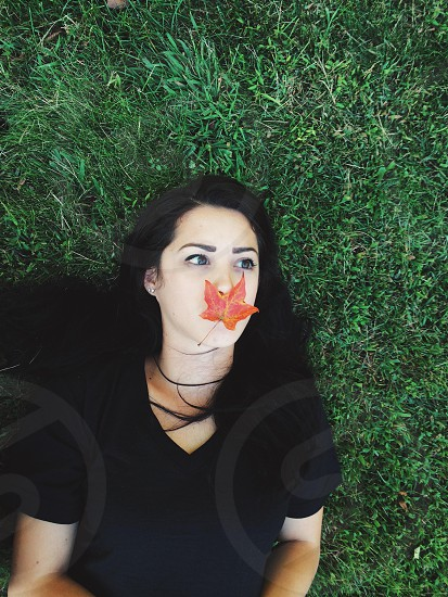 woman lying on green grass orange maple leaf photo