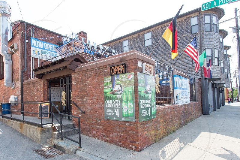 brown concrete brick building open restaurant with display of flags near gray pathway under blue bright sky photo