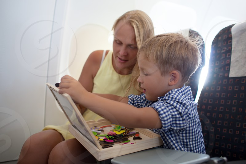 Mother and little son in the plane. They playing learning game with board and magnets photo