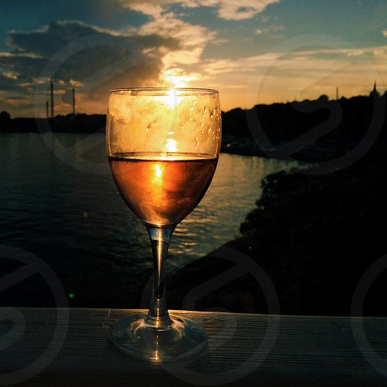 Sun shining through single glass of rose at sunset photo