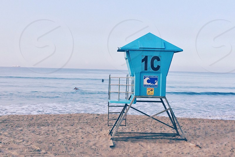blue and black lifeguard house near seashore photo