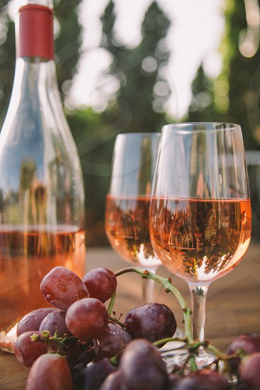 two wine glasses filled with rose wine on a table next to the bottle and purple table grapes surrounded by trees photo