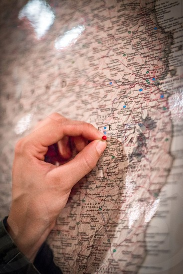 Hand inserting a push pin into a map. photo