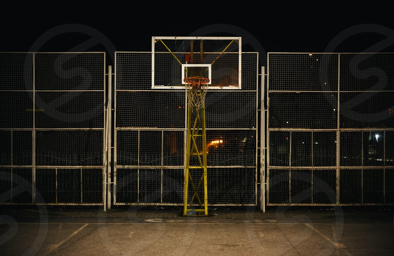 The basketball court during night view on basketball hoop and fence. photo