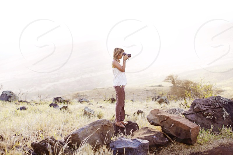woman in white blouse taking picture photo