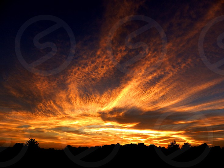 Sunset filling the sky across clouds in bursts of orange and yellow.  photo