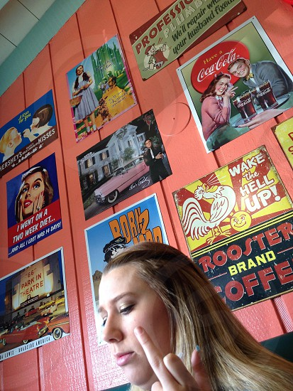 woman sitting underneath old posters photo