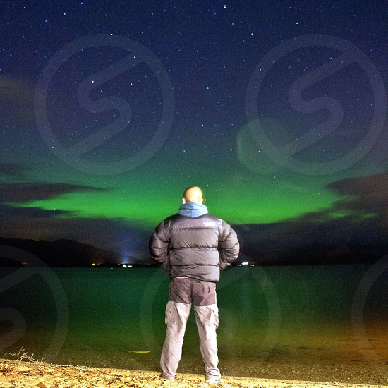 man wearing black bubble jacket standing near on lake with a view of houses under nightsky photo