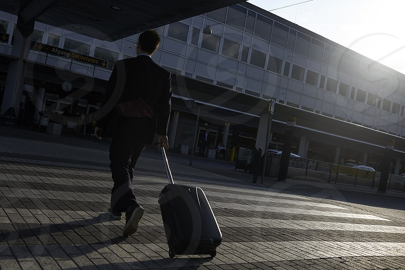 Businessman pulling his trolley luggage to enter the terminal at Copenhagen airport in early morning sunshine photo