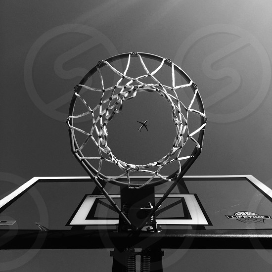 low angle grayscale photo of portable basketball hoop and airplane captures at the center of basketball hoop photo