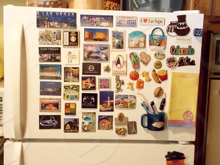 Magnet collection on the white refrigerator photo