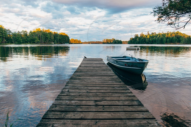 gray rowboat on brown wooden pier photo