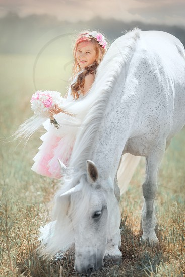 Girl with unicorn at sunrise  photo
