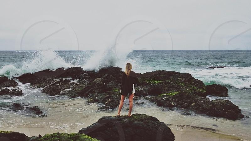 woman in black long sleeved shirt standing near ocean rock photo