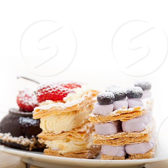 selection of fresh cream napoleon and chocolate mousse cake dessert plate  photo