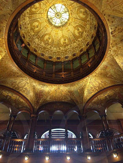 interior of gold building with dome roof and dark brown wood accents photo