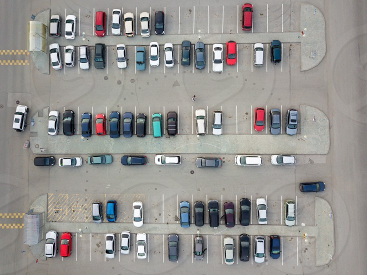 Aerial view of a large number of cars of different brands and colors standing in a parking lot near the shopping center in a chaotic manner. Parking divided by white dividing strips and sidewalks photo
