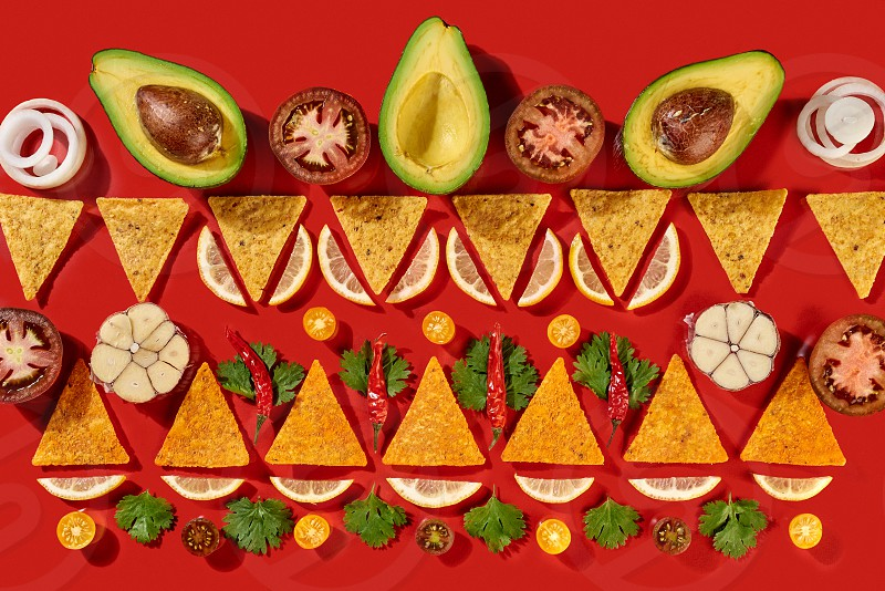 Ingredients of Guacamole dressing for mexican corn chips - avocado halves lemon slices garlic tomato parts onion  parsley green as a traditional pattern on a red background. Top view. photo