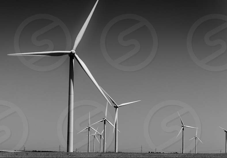 grayscale photography of wind turbines photo
