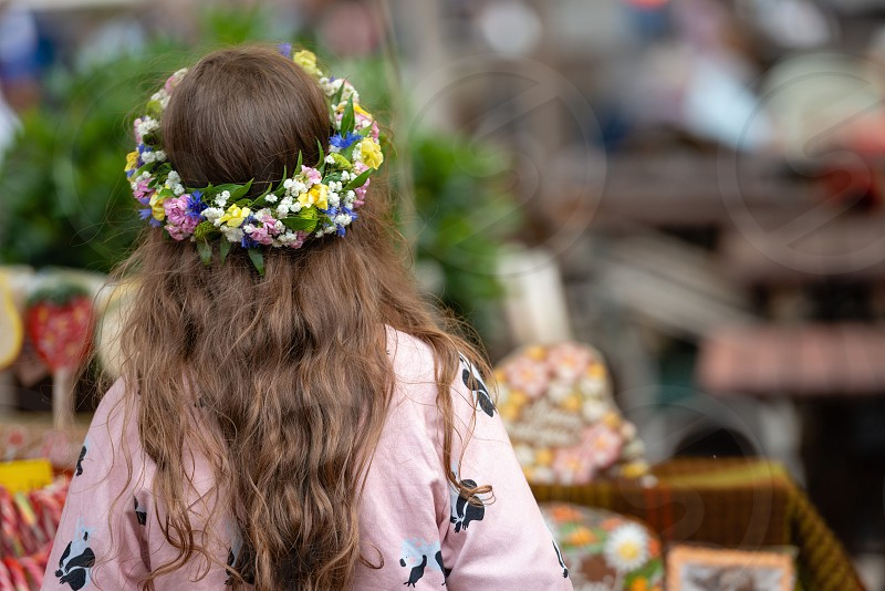 A girl with a crown of flowers looks forward. View from the back. photo