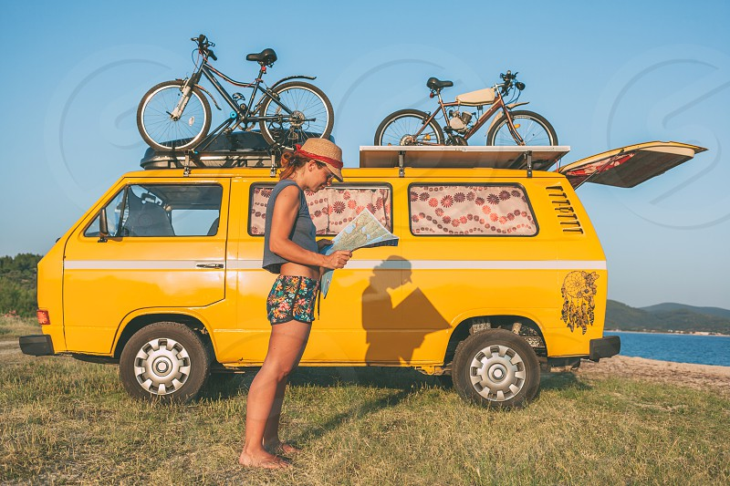 Summer holidays road trip vacation travel and people concept - young hippie women in front of minivan car on beach photo