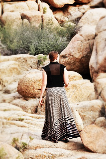 woman in black and grey striped maxi skirt walking photo