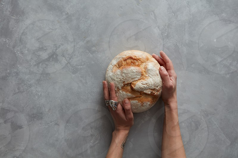 Baker man holding a beautiful round bread on a gray stone background photo