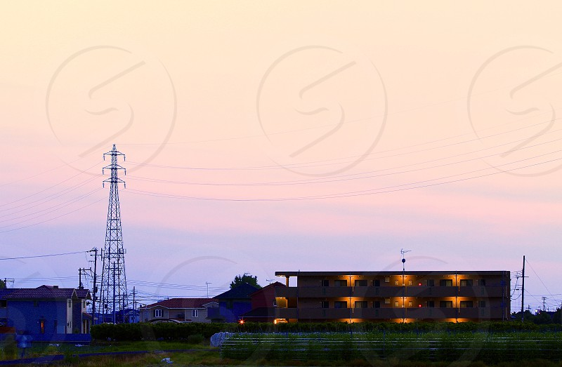 three story building in distance under blue and pink early evening sky photo