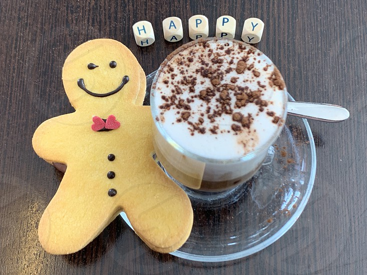 Happy breakfast with a funny pastry cappuccino and wooden letters at the bar photo