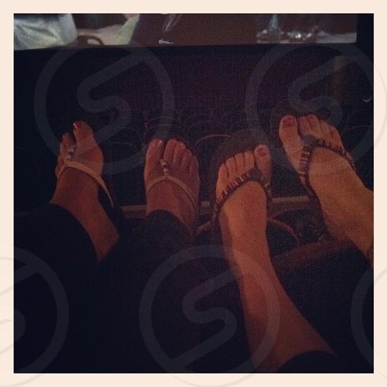 2 women sitting showing flip flops  photo