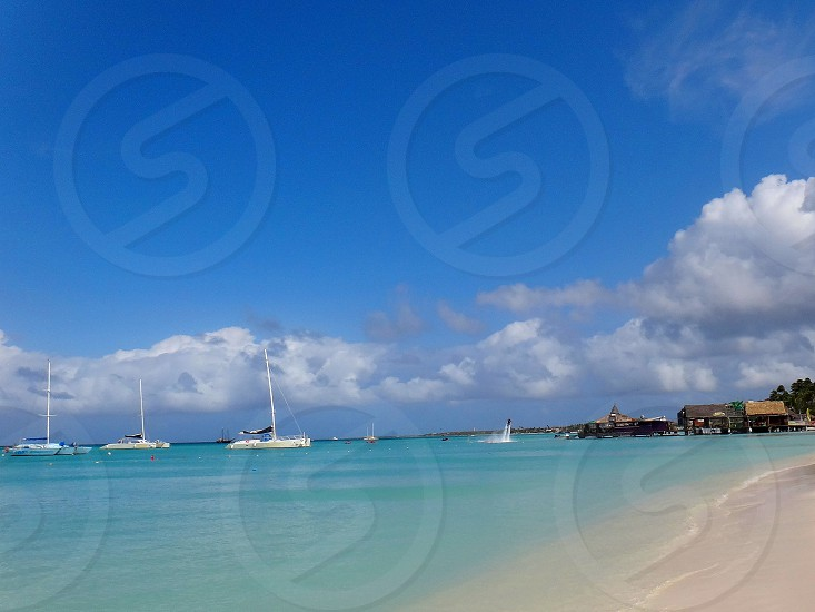 coast of aruba beach with sailing boats and extreme sports photo