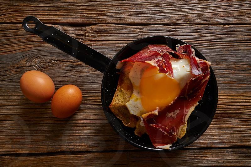 Tapas huevos rotos broken eggs with ham and yang from Spain photo