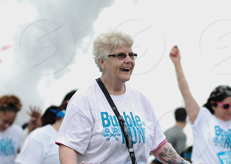 woman smiling with green pink arm tattoo wearing blue bubble nun printed on white t shirt black framed eyeglasses and black gray crossbody bag strap during daytime photo