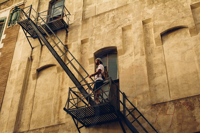 man in a backwards gray hat and a white short sleeved shirt standing on a fire escape photo