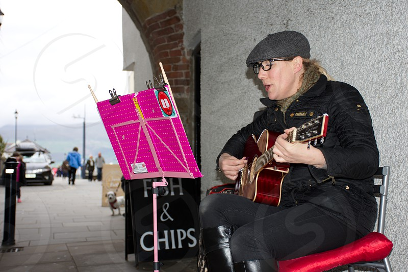 Street artist playing guitar and entertaining tourist on the streets of coastal town in uk.  photo