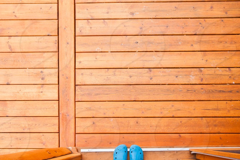 Feet in blue rubber shoes in open doorway onto wooden porch or deck from straight above with rich warm wood grain textures and colors photo