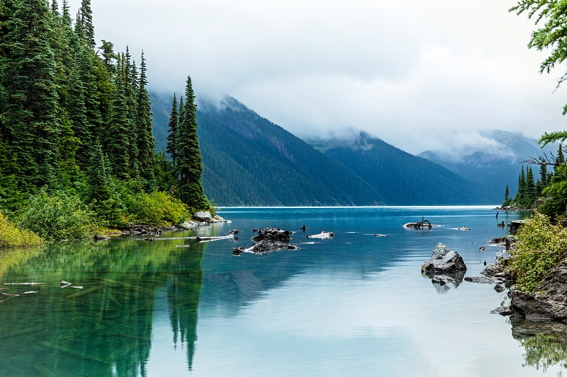 Reflections of Trees and Mountains in the turquoise colored Garibaldi Lake near Whistler British Columbia Canada. photo