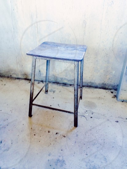 grey metal framed stool by the wall photo