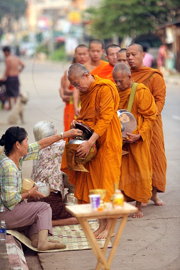 the monks on the tour in the morning in the city of Tha Khaek in central Lao in the region of Khammuan in Lao in Souteastasia. photo
