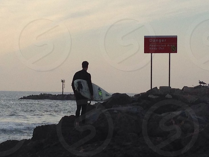 man holding white surfboard photo