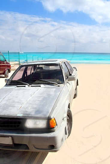 aged grunge car in Mexico Caribbean turquoise beach photo