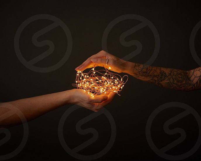 Bright yellow garland holds female hand with tattoo and male hand around a dark background with space for text. photo