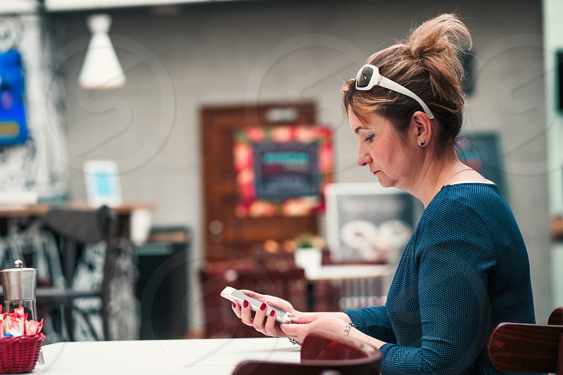 Young woman using mobile phone sitting by a table in cafe photo