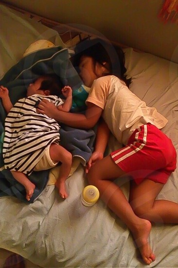 girl and baby sleeping on bed photo