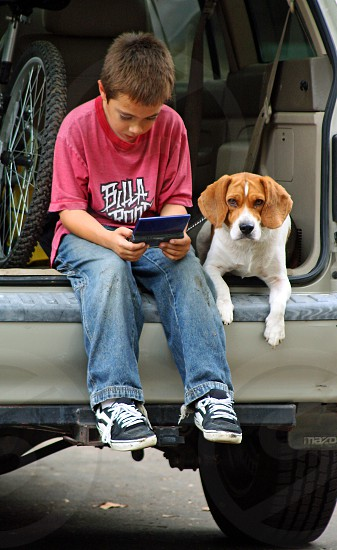 Boy and his dog sit in the back of an open van; he is playing a game as hisdog lays next to him looking at the camera photo