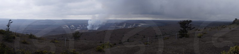 panorama photo of geothermal area with steams below cloudy sky during daytime photo