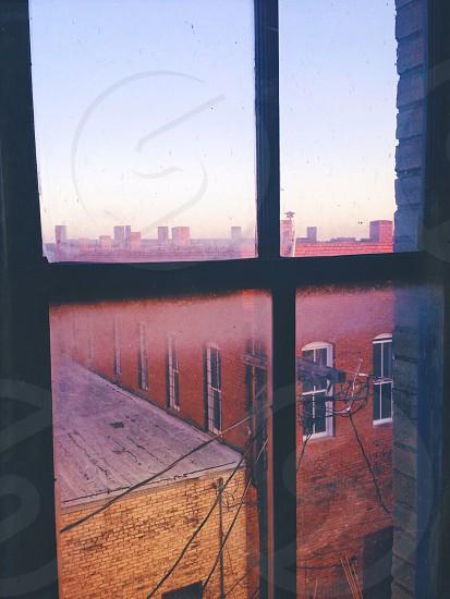 Brick buildings window window view window pane roof upstairs rooftop telephone wires sunset sky solitude secret. photo