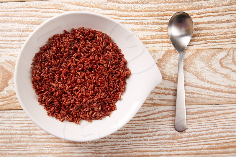 Red wild rice in a white plate over wooden board photo
