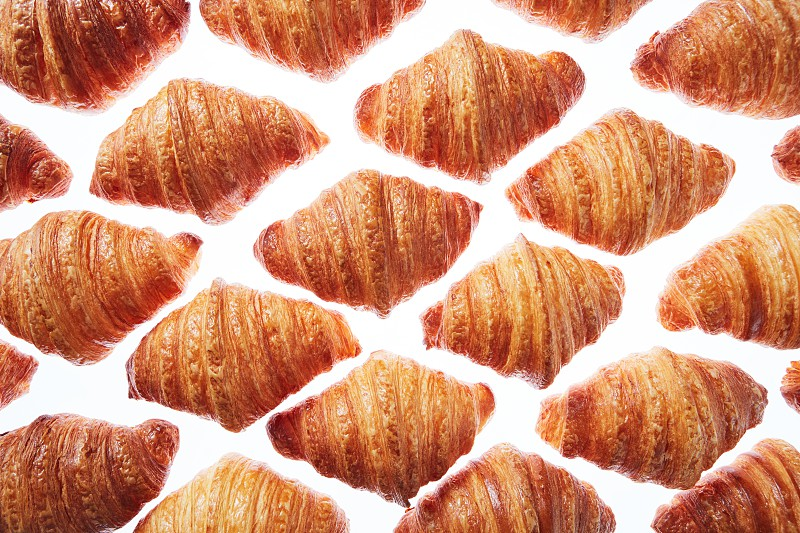 Fresh homemade french croissants on a white background. Rhombus diagonal pattern. Concept of continental breakfast. photo