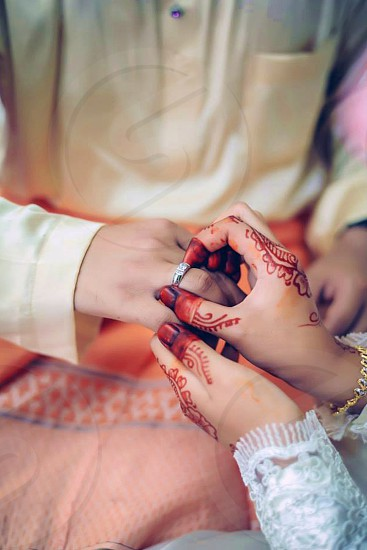 person in white long sleeves dress with mhendi tattoos in hands holding silver diamond ring in person's right hand wearing yellow long sleeves tops photo